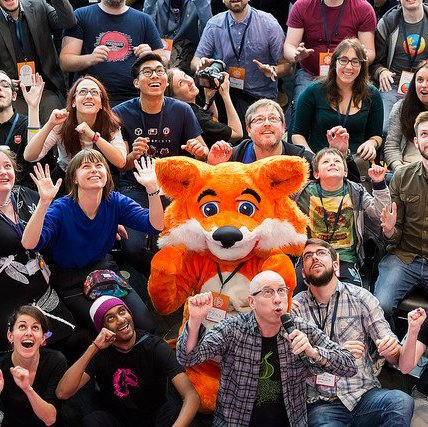 A group photo from the opening circle at MozFest, where everyone is making a fox gesture with the FireFox mascot in the middle of the image.