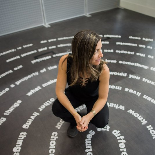 An artist, sitting with one of their art pieces, of various moral questions in the shape of a labyrinth on the floor.