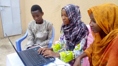 Chamsa Al Marif Nime, a Digital Grassroots Ambassador from Chad, sits with two other young people while they use a computer connected to a mobile internet modem.jpg