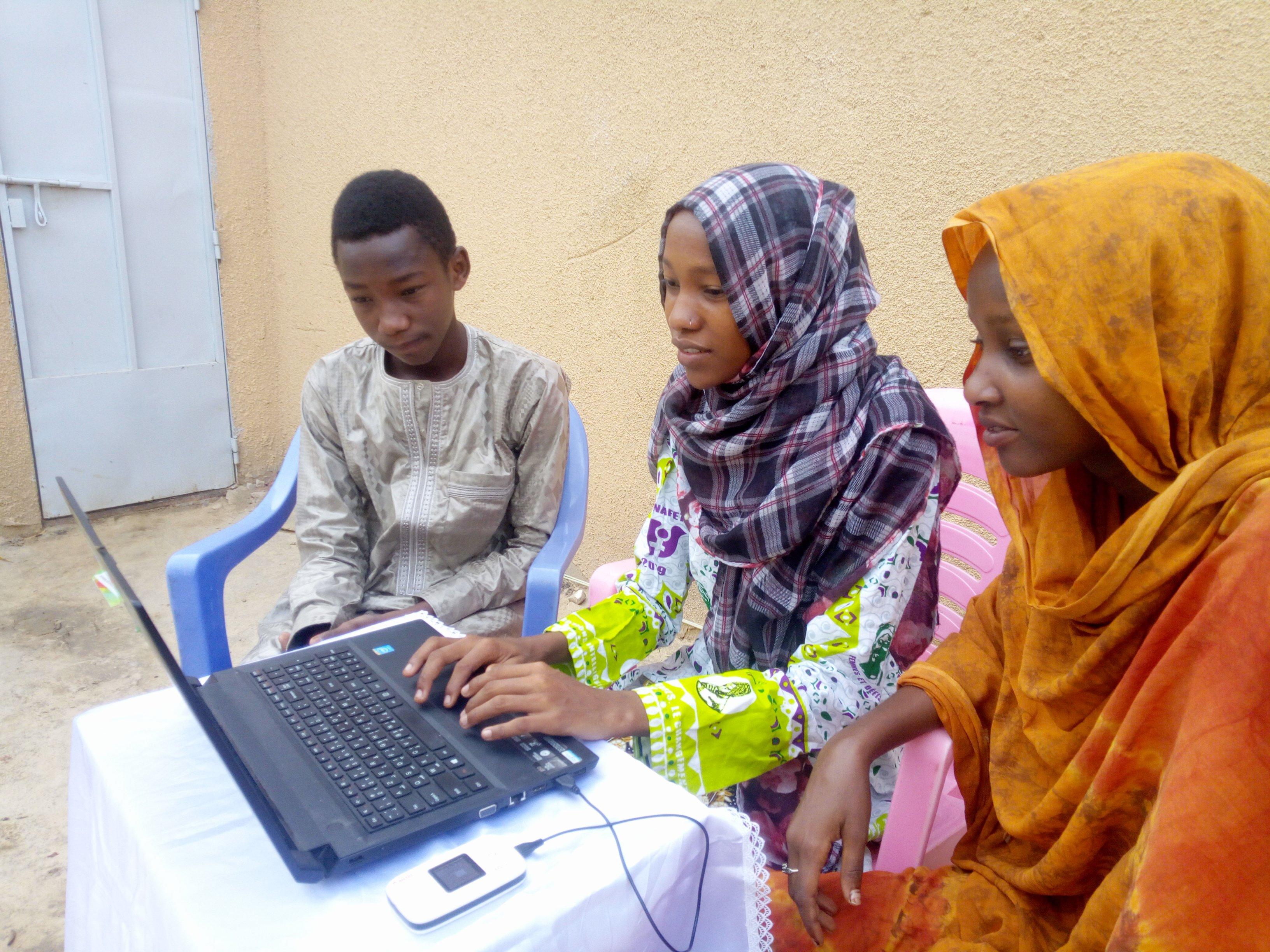 Chamsa Al Marif Nime, a Digital Grassroots Ambassador from Chad, sits with two other young people as they use a computer connected to a mobile internet modem