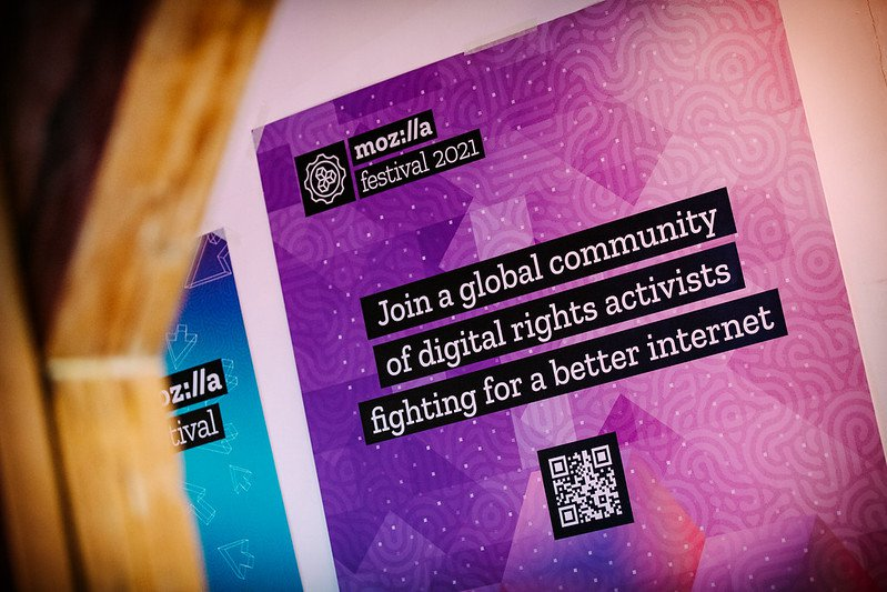 """Purple and pink poster hanging on a wall with Mozilla Festival 2021logo in the upper right corner and text """"Join a global community of digital rights activists fighting for a better internet"""" and a QR code at the bottom"""