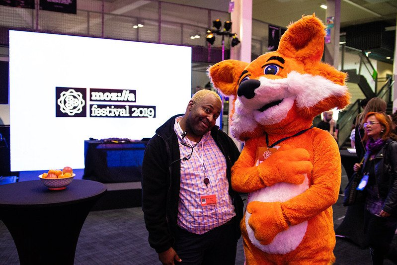 MozFest Volunteer in black sweater and plaid shirt standing next to person in foxy costume, smiling at the camera