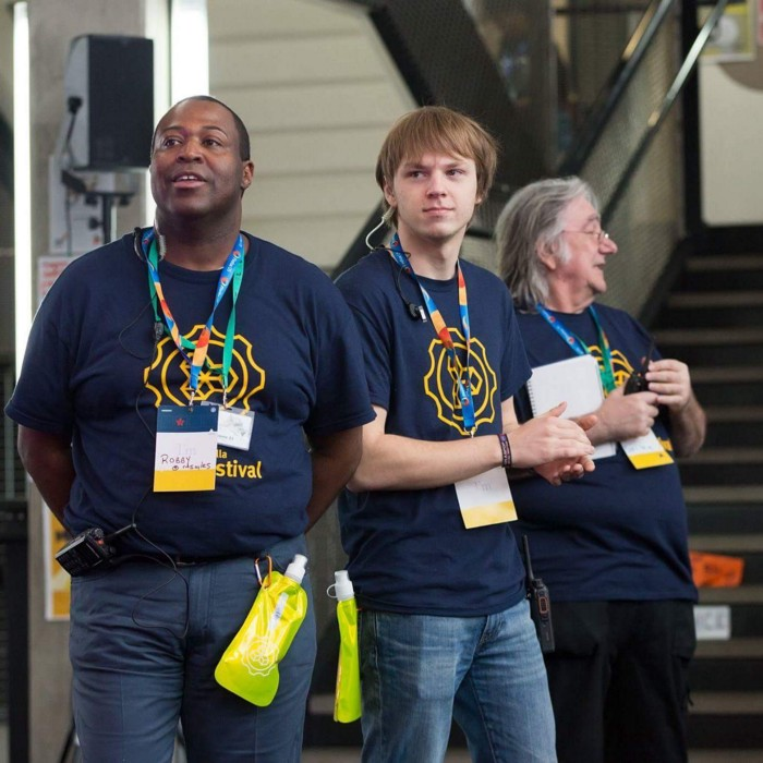 Three volunteers at MozFest wearing blue festival shirts and name tag lanyards.