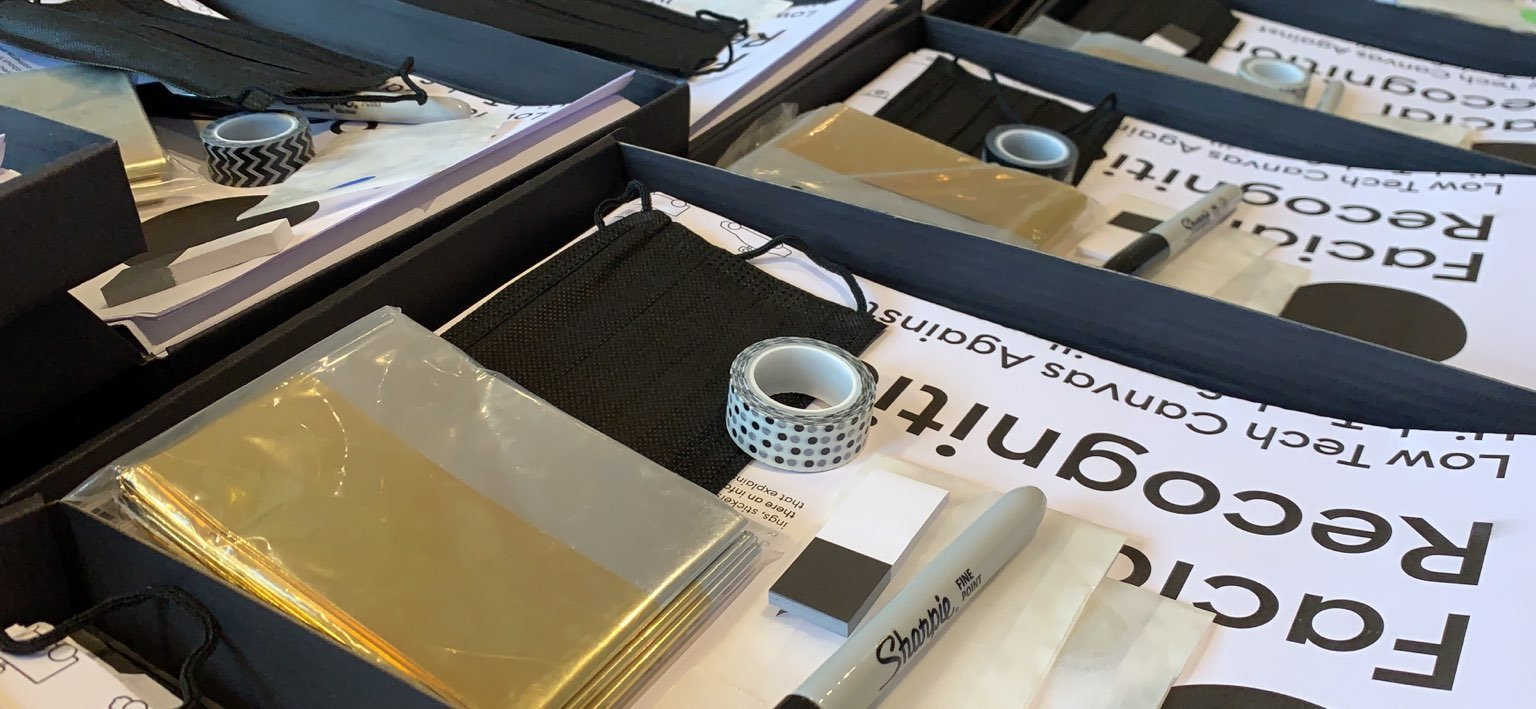 An image of materials laid out on a table - includes paper, canvas, tape, and a black marker