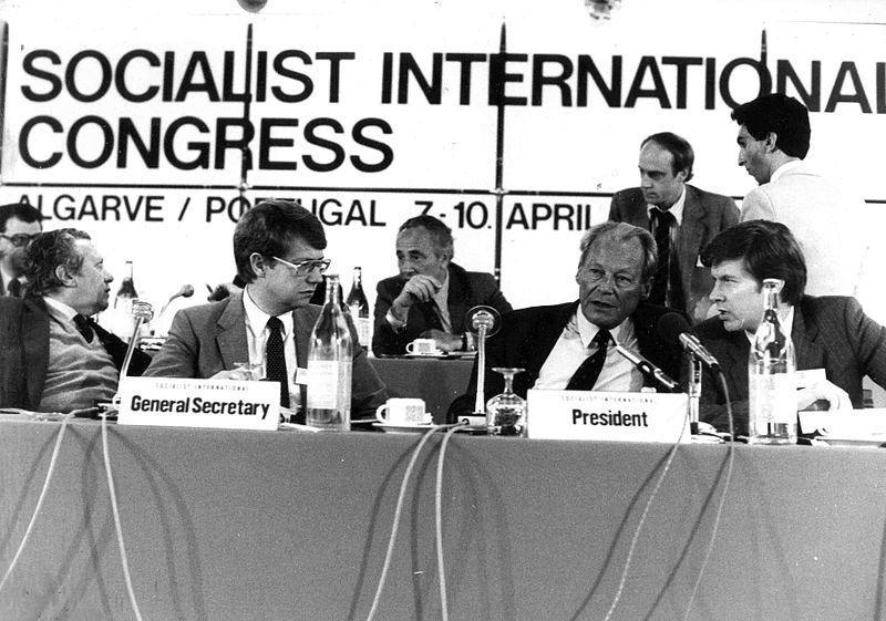 """Black and white photo of a group of men sitting at a long table with the text """"Socialist International Congress"""" in big bold letters in the background.  ."""