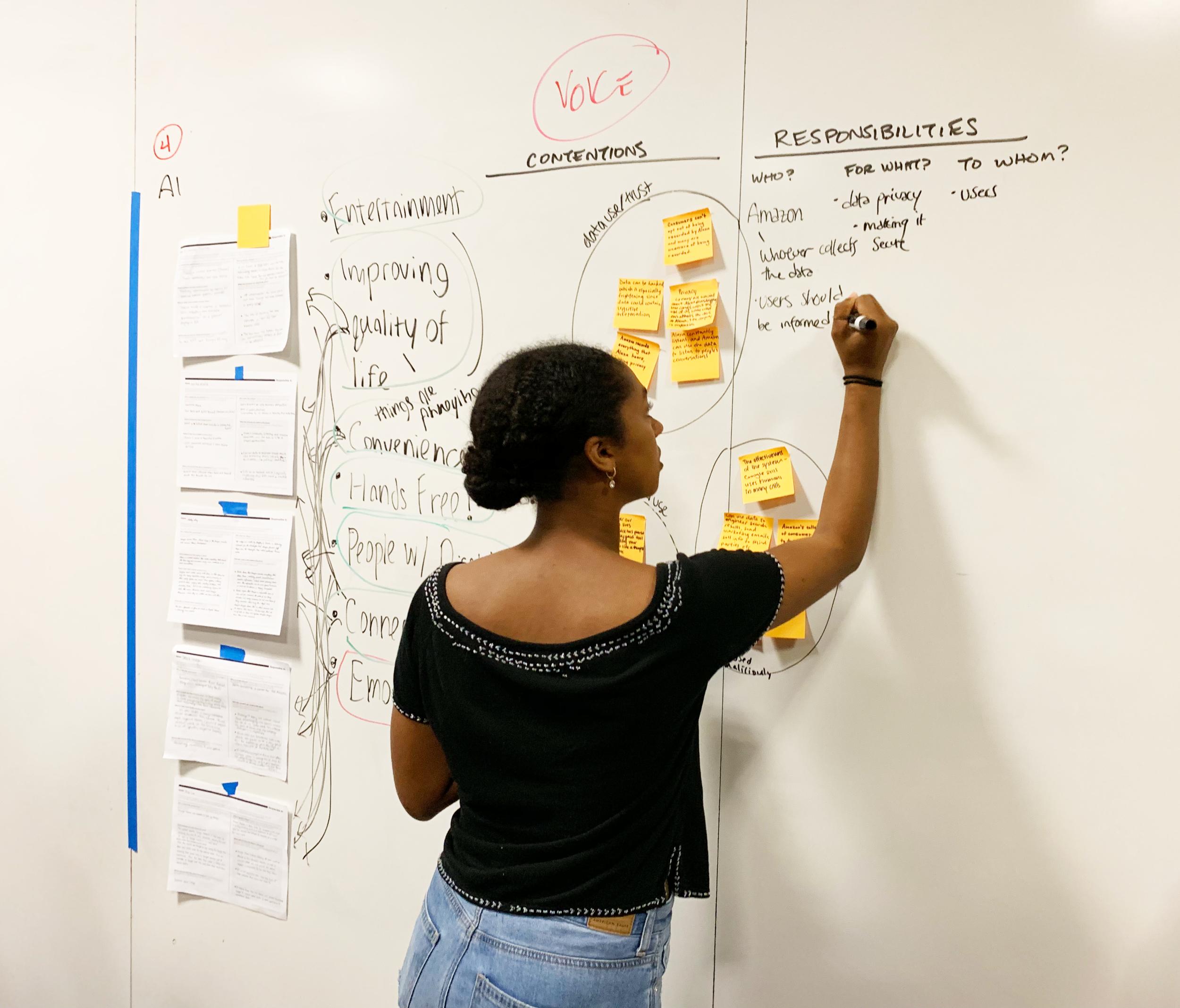 Woman writes on white board.