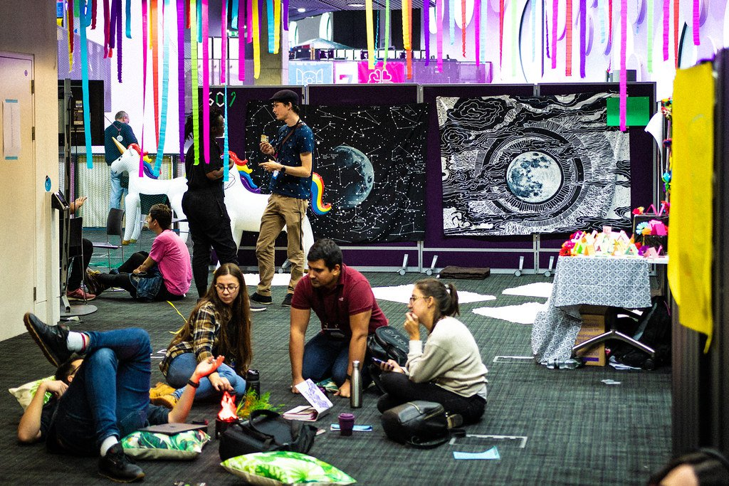 MozFest participants stand and sit together in the open spaces of the festival, continuing conversations from sessions. Brightly colored streamers, workshop materials, and even an inflated unicorn are in the background.