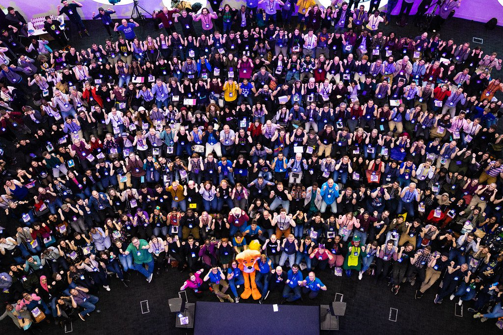 An overhead shot, taken from several floors above, of the MozFest 2019 plenary audience, which is seated in long rows of chairs arranged in a semi circle facing a small stage at the bottom center of the photo, and with everyone looking up at the camera with silly, scary faces and poses as if they were pretending to be monsters.
