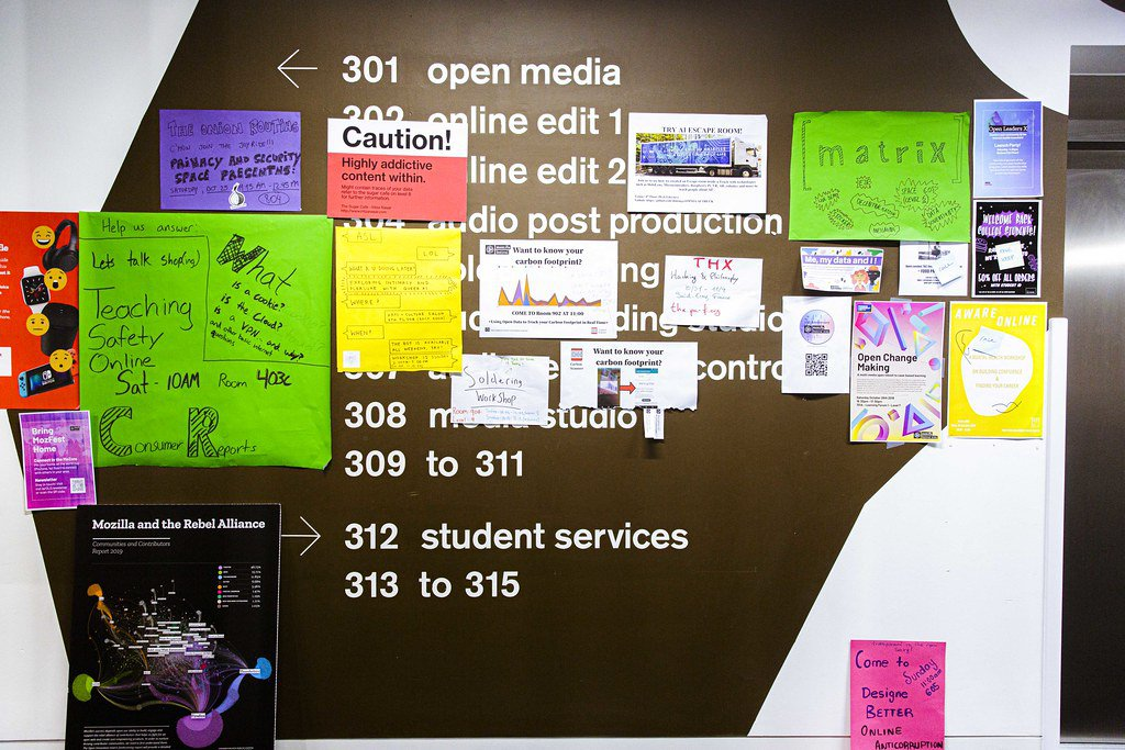 """An image of a wall that's been painted brown with white lettering to list a directory of rooms on the 3rd floor of Ravensbourne University in London with brightly multi-colored MozFest session posters stuck on top of it sharing session titles like """"Teaching safety online,"""" """"Caution! Highly addictive content within,"""" and """"Open change making."""""""