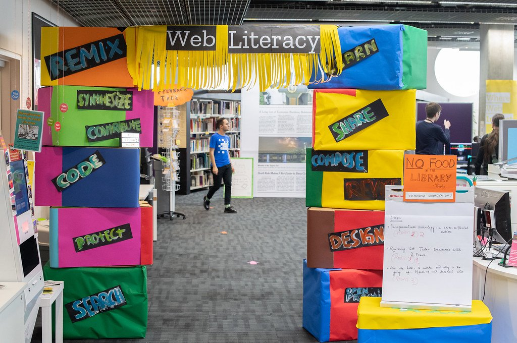 """An image of cardboard boxes stacked and stuck together to make a squared arch with each box covered in brightly colored construction paper signs with words like, """"Web Literacy,"""" """"Learn,"""" and """"Remix."""""""