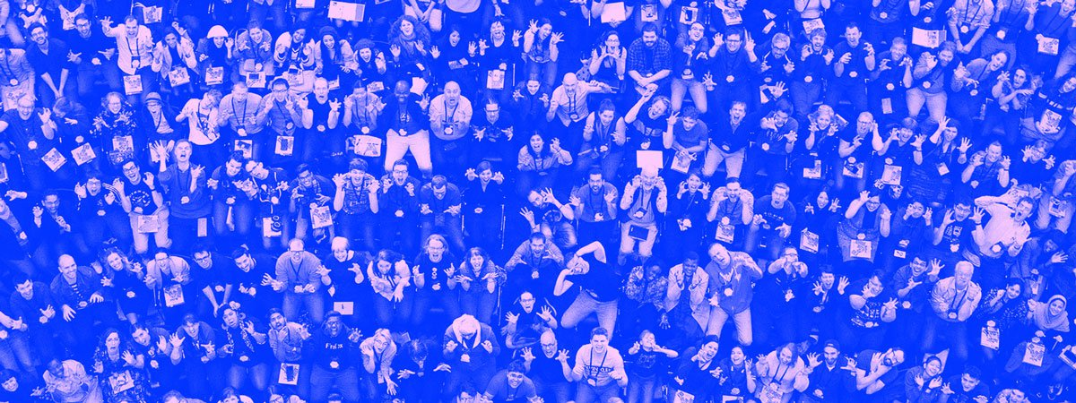 A group photo, taken from above, of hundreds of MozFest attendees sitting in chairs arranged in a semi-circle in front of a small plenary stage.