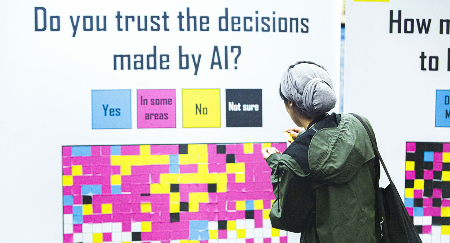 "A person in front of a big panel full of post-its that says ""do you trust the decisions made by AI?"""
